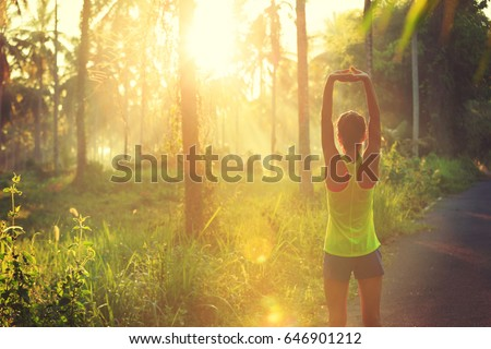 Young female runner warming up before running at morning forest trail #646901212