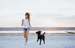 Young female running with labrador retriever dog on the beach at sunset
