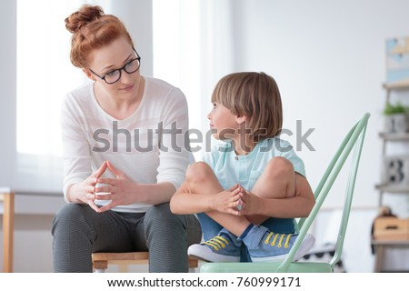 Young female school psychologist having serious conversation with smart little boy at her office #760999171
