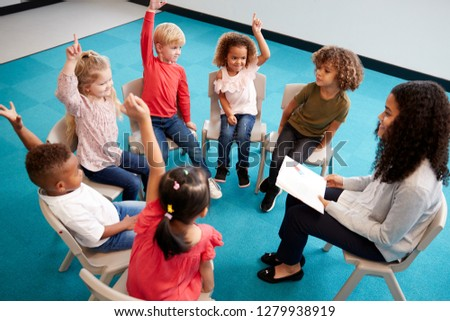 Young female school teacher reading a book to infant school children, sitting on chairs in a circle in the classroom raising hands to answer a question, elevated view