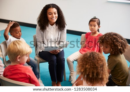Young female school teacher reading a book to kindergarten children, sitting on chairs in a circle in the classroom listening, close up