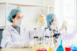Young female scientist in protective glasses and gloves testing tube chemical ingredient to conduct research in laboratory,test sample antibiotics and future food use in medical development for people