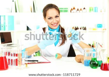 Young female scientist injecting GMO into   potato in  laboratory