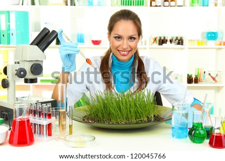 Young female scientist is conducting experiments with plants in  laboratory