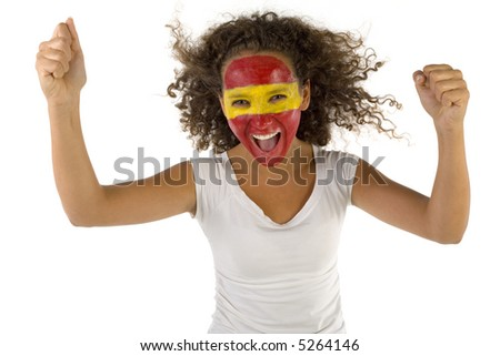 Young female screaming Spanish fan with hands up and painted flag on faces. She's on white background. Front view. She's looking at camera.