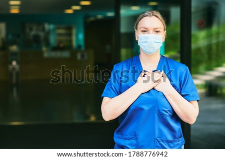 Young female scrub nurse wear blue uniform and face mask, standing in hospital entrance