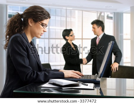 Young female secretary makes notes on a laptop  while other business people are shaking hands in the background. Daylight, indoor, office.