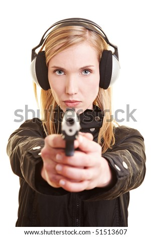 Young female shooter with pistol and ear protection