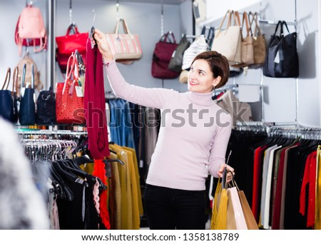 Young female shopper buys blouses women's clothing store