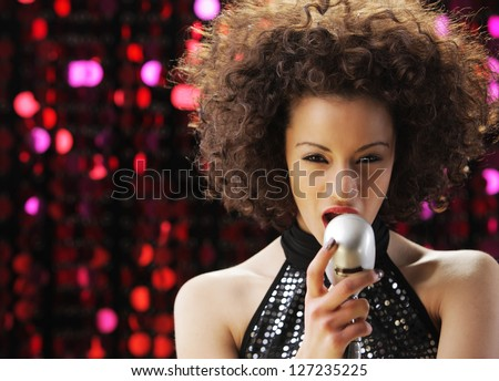 Young female singer with brown curly hair singing a song