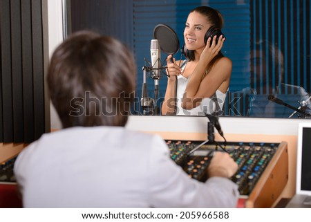 Young female singer with studio technician in foreground at the recording studio