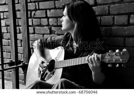 Young female sitting against brick wall and playing guitar while looking through bars.