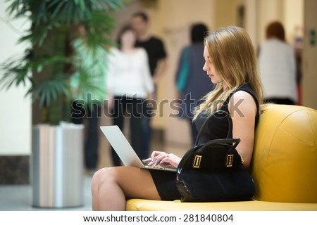 Young female sitting on yellow coach working on laptop in public wifi area, typing, people passing by on the background