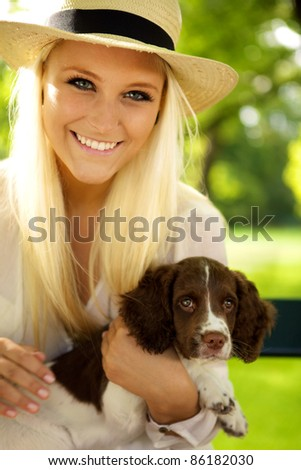 Young female sitting with a puppy on a park bench.