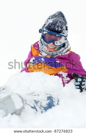 Young female skier fallen in the deep snow