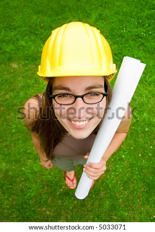 young female smiling architect or builder wearing a yellow hart hat holding architectural plans