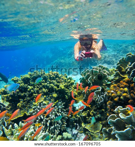 Young female snorkler, takes pictures of the underwater world.