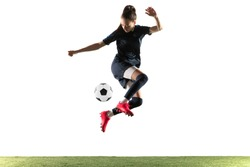 Young female soccer or football player with long hair in sportwear and boots kicking ball for the goal in jump isolated on white background. Concept of healthy lifestyle, professional sport, hobby.