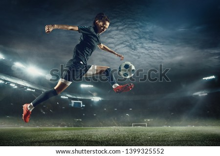 Young female soccer or football player with long hair in sportwear and boots kicking ball for the goal in jump at the stadium. Concept of healthy lifestyle, professional sport, hobby, motion, movement #1399325552
