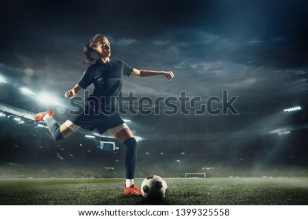 Young female soccer or football player with long hair in sportwear and boots kicking ball for the goal in jump at the stadium. Concept of healthy lifestyle, professional sport, hobby, motion, movement