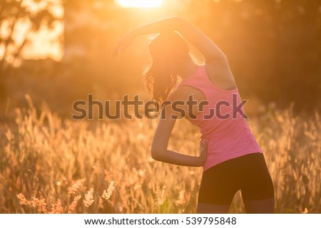 Young female  stretching before fitness training session at the park. Healthy young woman warming up outdoors. She is stretching her arms and looking away. #539795848