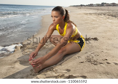 young female stretching outside on the beach