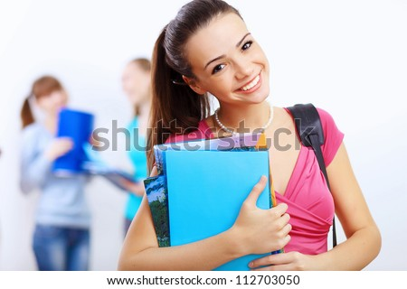 Young female student at college with books