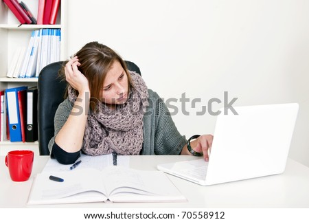 Young female student doing internet research whilst studying her textbooks behind her desk