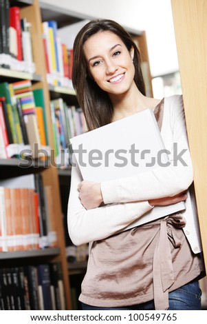 young female student holding book in library