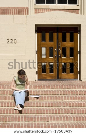 Young female student is reading on the steps in the college campus