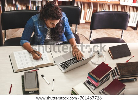 Young female student study in the school  library.She using laptop and learning online. #701467726