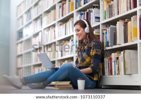 Young female student studying in the library #1073110337