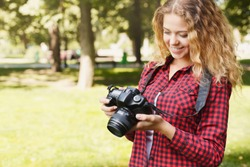 Young female student taking photos in the park with camera. Photography classes, education and remote working concept, copy space, closeup