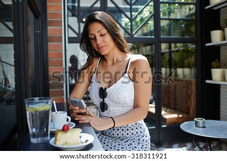 Young female student use mobile Internet on smart phone to correspond with her friends in chat,modern arabic women typing text message on cellphone while breakfast at sidewalk cafe in sunny summer day #318311921
