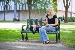 Young female student using cell phone while sitting in college campus