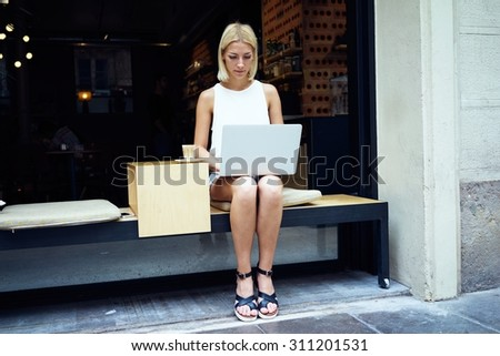 Young female student work on net-book during breakfast in coffee shop, caucasian woman using modern devices for distance work