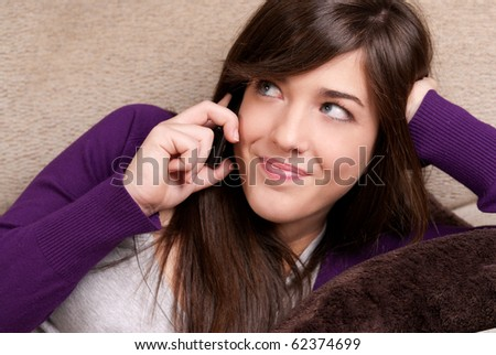 Young female talking by telephone smiling lying on couch close-up