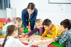 Young female teacher and happy schoolkids playing interesting board game during lesson in classroom