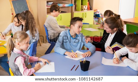 Young female teacher and pupils working in classroom at elementary school  #1081142687