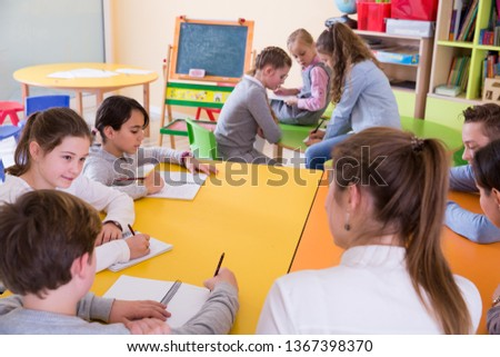 Young female teacher and pupils working in classroom at elementary school #1367398370