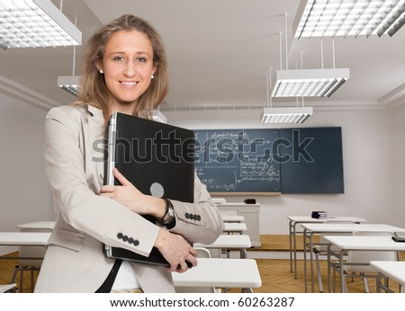 Young female teacher holding a laptop in a classroom