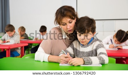 Young female teacher working with pupils in classroom at elementary school #1306792420