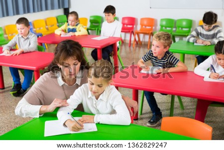 Young female teacher working with pupils in classroom at elementary school #1362829247