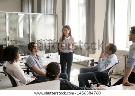 Young female team leader talk holding company informal office meeting, millennial woman speak at group briefing in coworking space, diverse employees brainstorm together discussing business plans