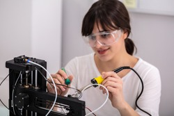 Young Female Technician Wearing Safety Eyeglasses Using Soldering Iron