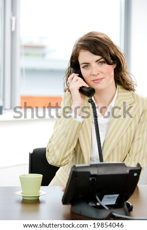 Young female telephone worker holding landline phone at office, smiling.