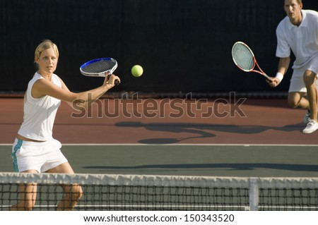 Young female tennis player hitting ball with doubles partner standing in background