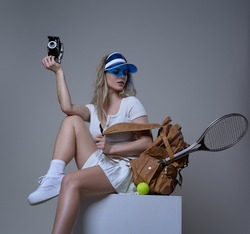 Young female tennis player sits on box holding photocamera and backpack with racquet and tennis ball in white background.