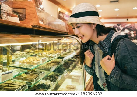 young female tourist choosing cakes of the desserts shelf in the chocolate factory while sightseeing.