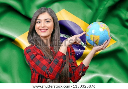 Young female Tourist holding Earth Globe against flag of Brazil #1150325876